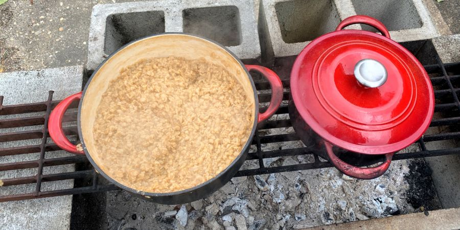 Two red Dutch oven pots, one with the lid on, standing on a grate suspended over hot coals.