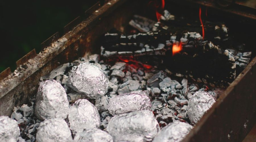 Potatoes wrapped in foil cooking on a charcoal grill.