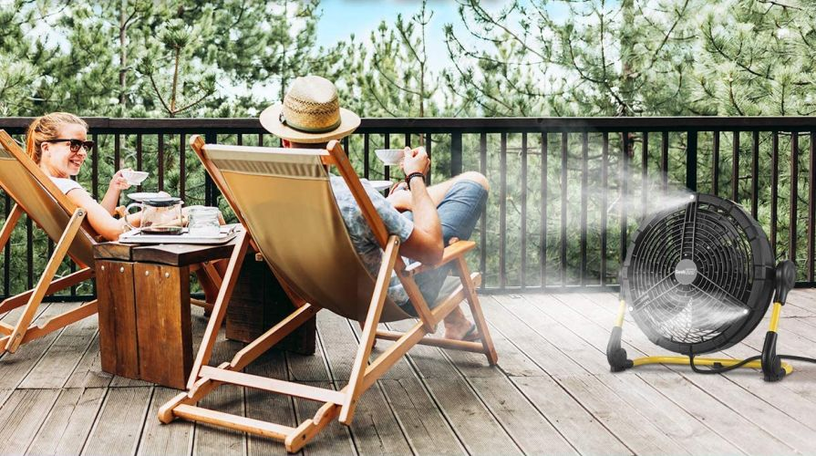 Couple sitting on a porch enjoying coffee and the cool breeze of a Geek Aire misting fan.