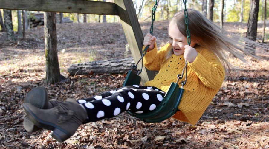 Girl swinging wildly on a swing set.