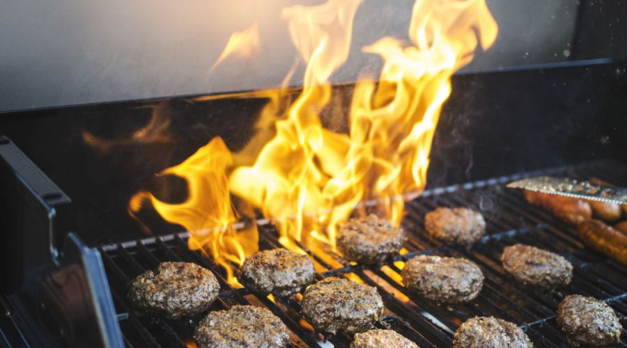 Fire flare-up on a grill with burgers on the grates.