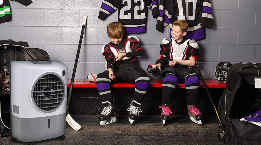 Two kids in ice hockey gear sitting on a red bench in an ice hockey change room with an evaporative cooler next to them.