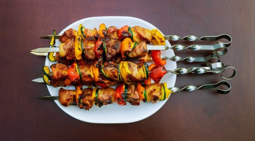 Grilled meat and vegetables pierced on a metal skewers.