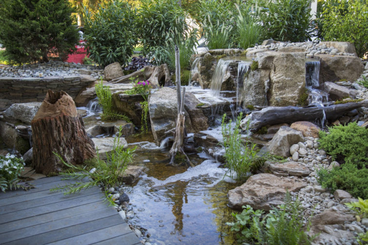 large water feature with multiple waterfalls and plants