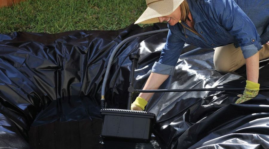 Woman installing a Pond Boss filter kit in a brand new pond.
