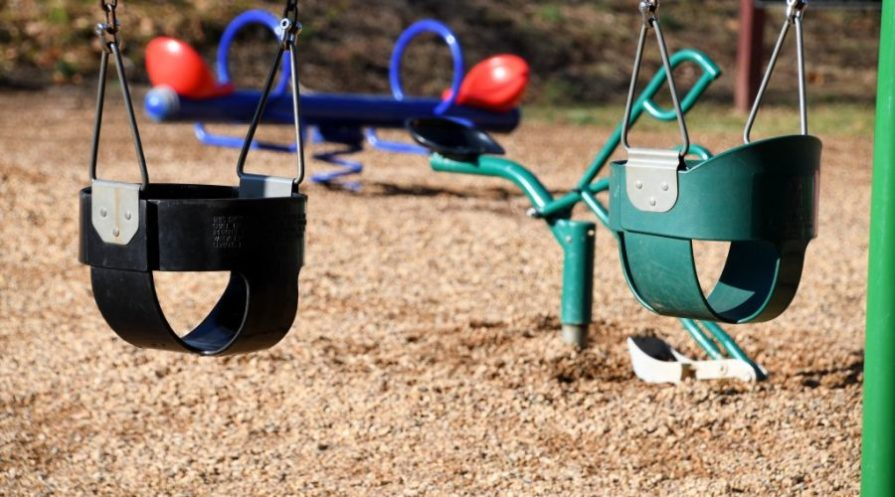 Empty swing set on a playground with sand coverage.