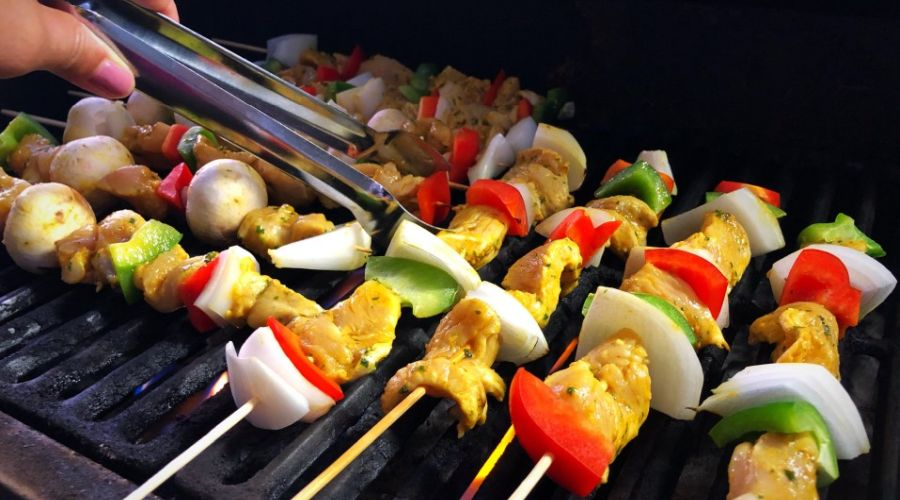 Veggies and meat pieces pierced on wooden skewers being turned with tongs while cooking on a BBQ grill.