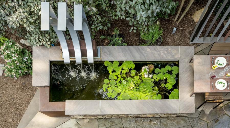 Large trendy backyard concrete paver patio fountain