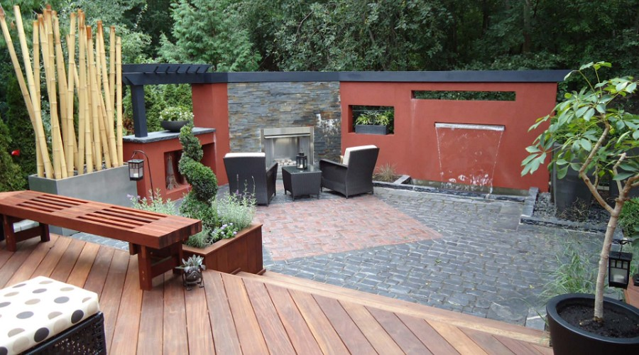 large trendy backyard stone patio fountain design