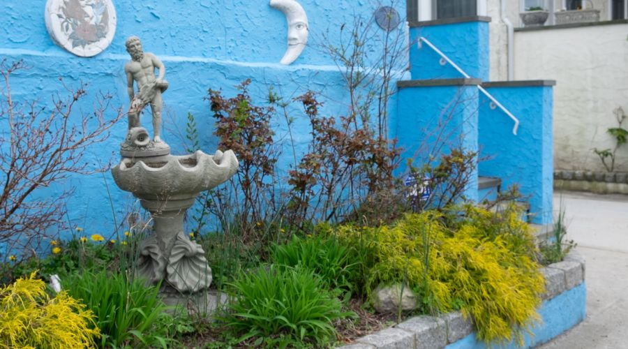 Water fountain in the front yard of a blue house.