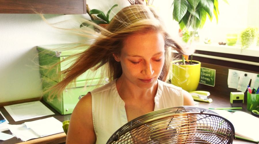 Woman in her office cooling off in front of a fan.