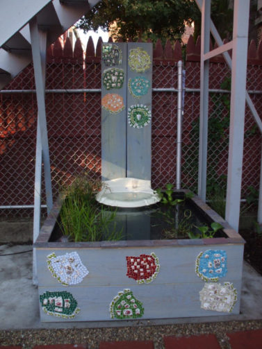wooden box koi pond using upcycled sink for fountain