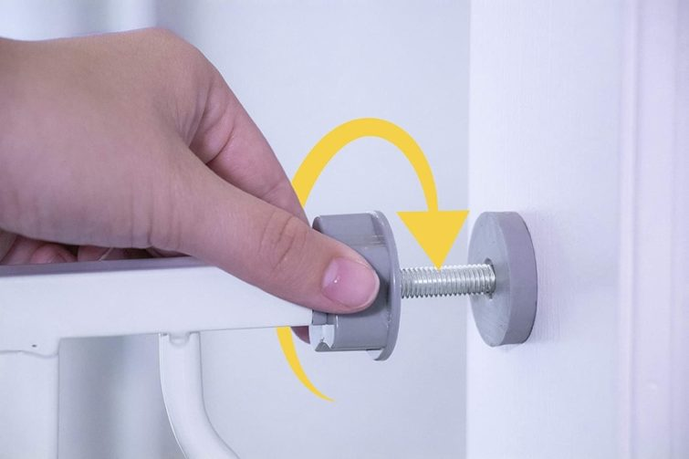 A pressure-mounting bracket that holds a baby gate in place against the wall.