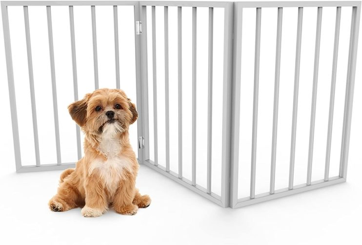 A young blonde and dog with a white chest sits in front of a white freestanding tri-folding dog gate.