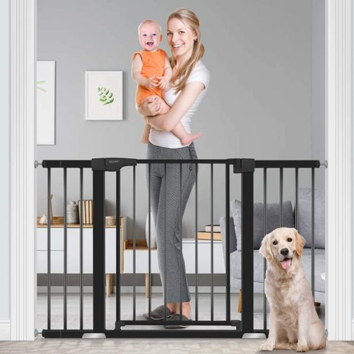 A woman with red hair, with baby in hand, stand on one side of an extra-wide black dog gate, and a blonde dog sits calmly on the other side.