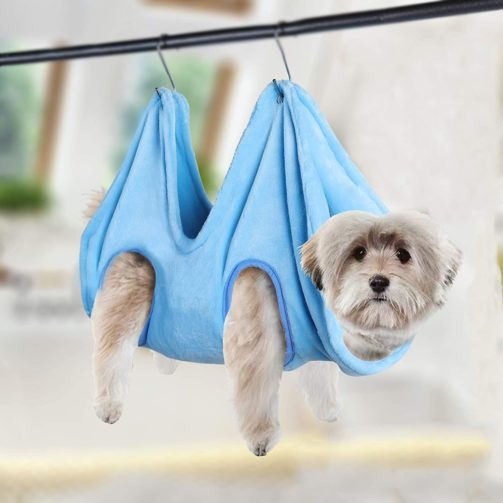 A small grey dog is in a light blue grooming hammock, hanging from a black bar.