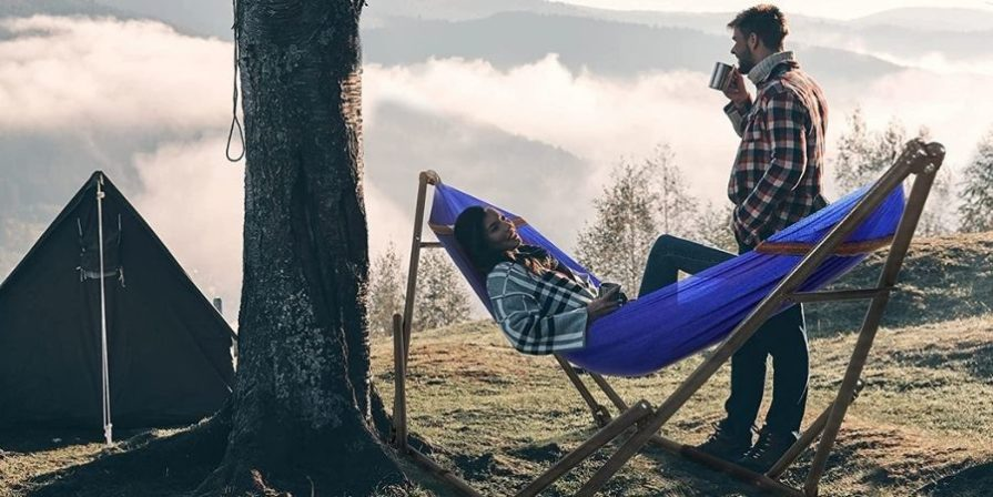 A woman wearing a black and white plaid shirt and jeans is laying in a blue hammock hung on a steel hammock stand next to a tree and a tent. A man in a red, black and white shirt is standing next to her drinking from a silver mug.