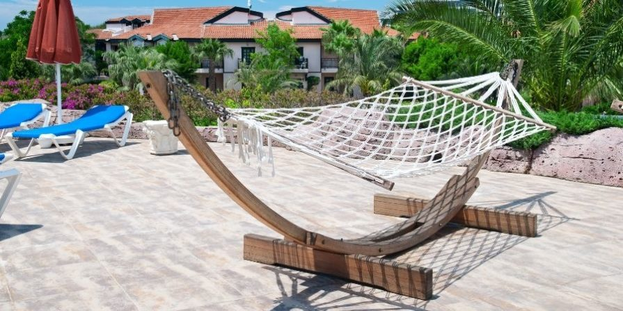 a wooden hammock stand on a stone tile patio area, holding a white rope hammock