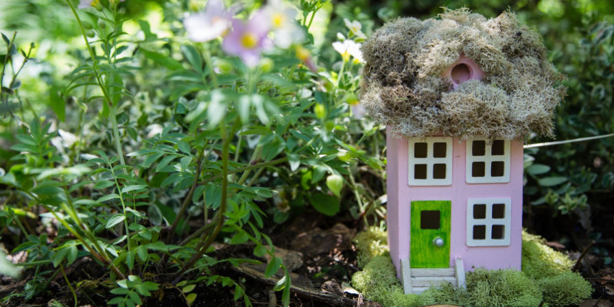 pink birdhouse with moss on roof, painted to look like tiny home, greenery in background