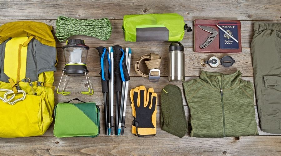 An assortment of camping gear is laid out on a wooden plank surface including a hiking pack, lantern, rope, knife, clothing, passport, water bottle, stool and gloves.