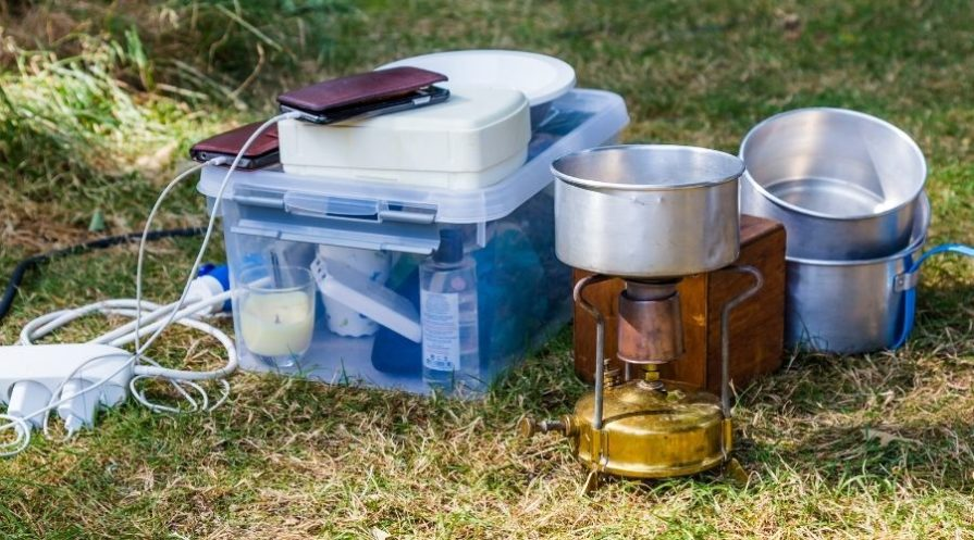 A variety of camping pots and other camp cooking supplies sitting in the grass next to a clear plastic storage tote full of smaller camping-related items