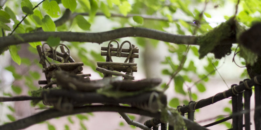 tiny furniture made of vine resting on branch of tree