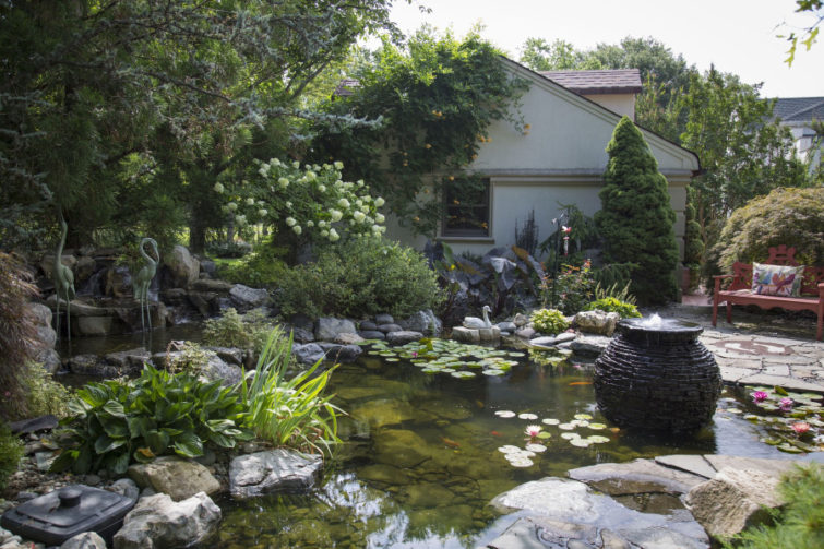 koi pond at edge of patio with fountain, waterfall, statues, and plants