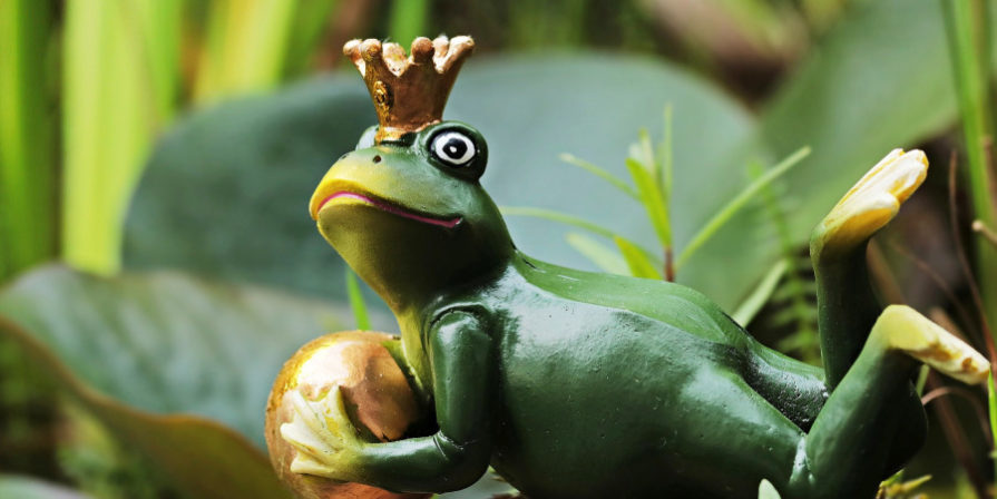 lounging frog prince statue in garden