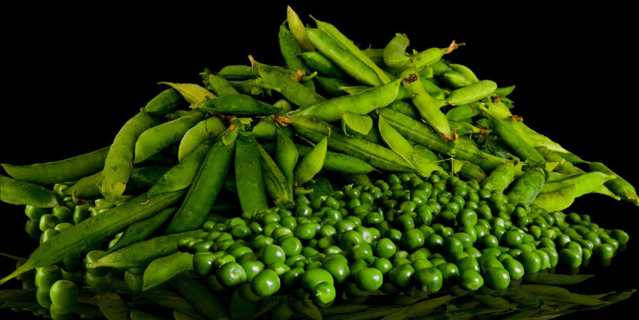 shelled and unshelled peas piled together on black background