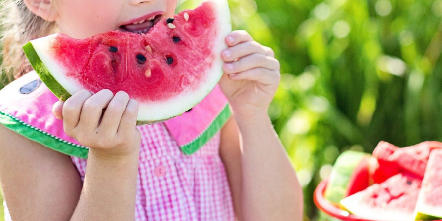 young girl dressed in pink eating a slice of watermelon