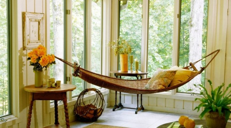A brown woven hammock hanging indoors from hooks in the wall, pillows in the hammock and plants all around it.