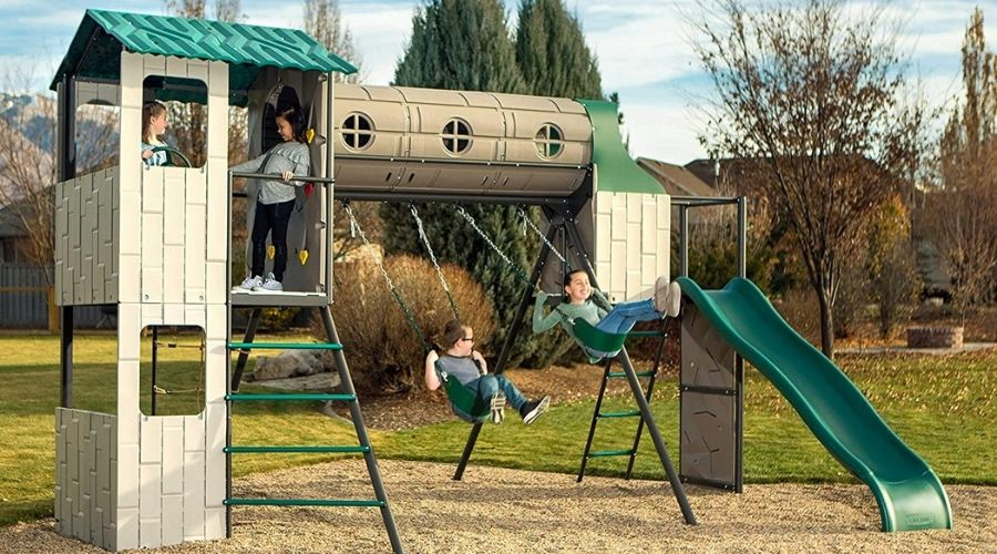 A group of 4 children are playing on a tan and green playset, two boys swinging on the swing set and two girls standing in the clubhouse on the side