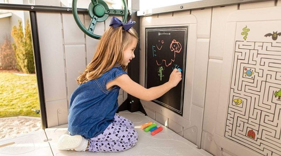 A young girl with long light brown hair is sitting inside a tan playset, drawing on a small chalkboard with a piece of blue sidewalk chalk