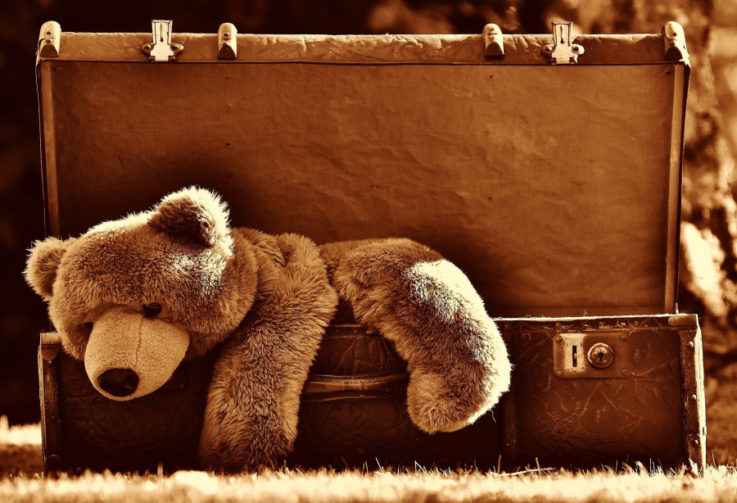 Brown teddy bear hanging halfway out of vintage suitcase