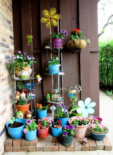 container garden on patio with flowers, fairy garden pieces, solar lights, spinners, and more against wood panel wall