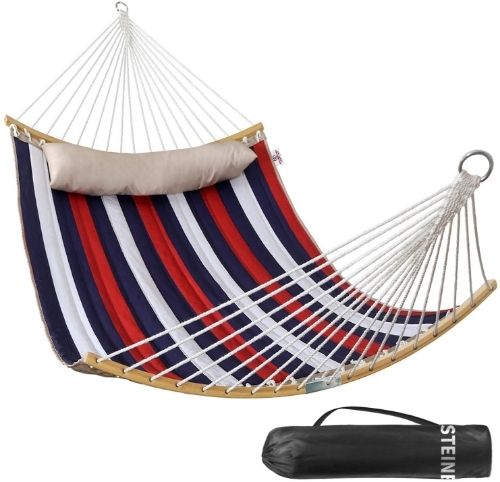 A red, white and navy blue quilted hammock with an off-white pillow and a black carry bag.
