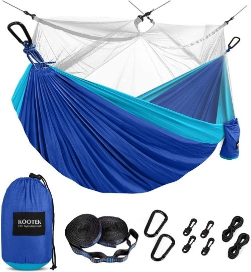 A two-tone blue parachute hammock with a bug net suspended over top. Beneath it, a blue stuff sack, 2 tree straps, carabineers and ropes are displayed.