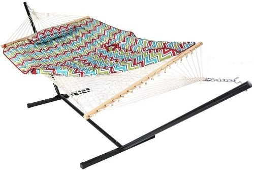 A white rope style hammock hanging from a black metal hammock stand. On the hammock is a green, blue and pink chevron hammock pad and pillow.