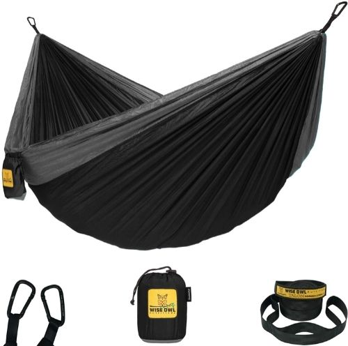 A black and grey parachute-style hammock with a black stuff sack, 2 black tree straps and 2 black carabineers.