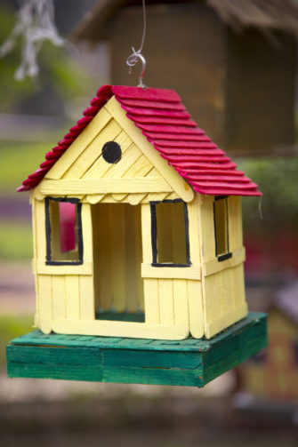 yellow, red, and green popsicle birdhouse or fairyhouse hanging from wire