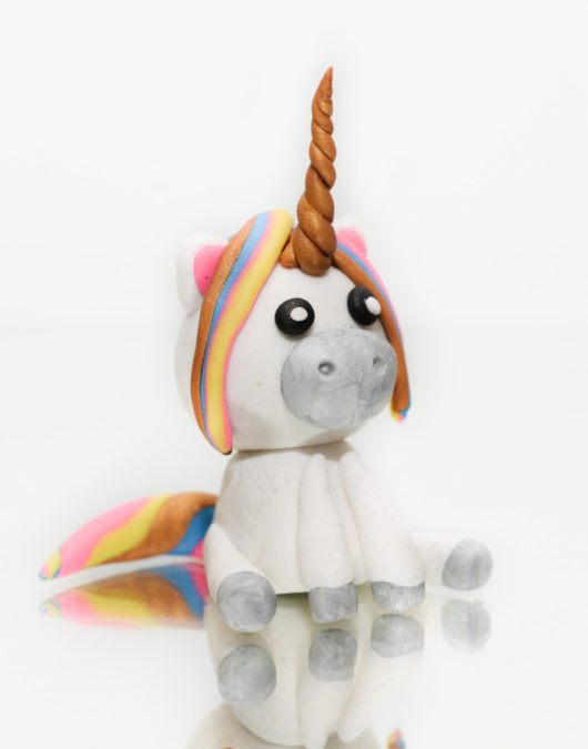 Mini polymer clay white unicorn with colorful hair and golden horn sitting on mirror