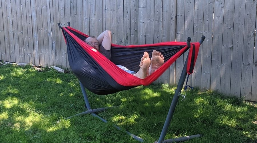 a man sleeping in a red and black hammock