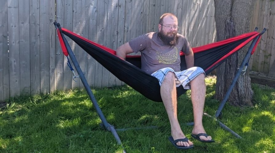 A man getting into a red and black hammock.