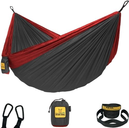 a dark grey and red parachute-style camping hammock with the carabineers, stuff sack and tree straps on display beneath it