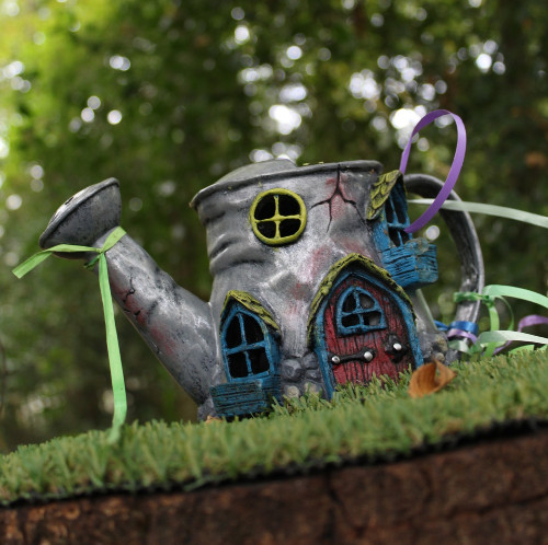 old watering can turned into fairy house