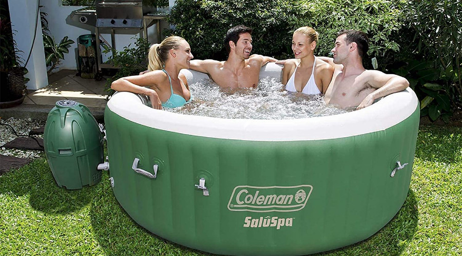 Two women and two men in inflatable hot tub on grass, trees in background