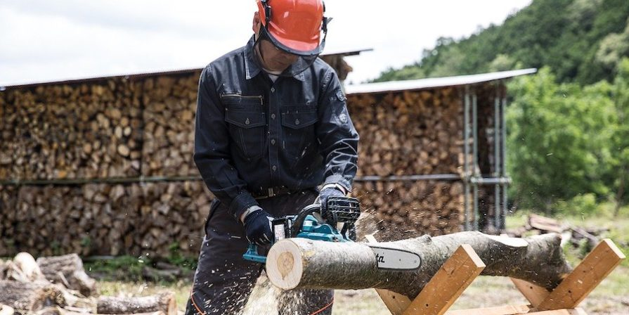 Man In Hard Hat Using Chainsaw