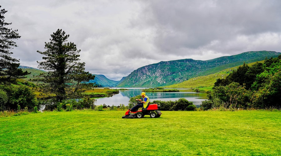 Person Mowing Lawn Near Lake