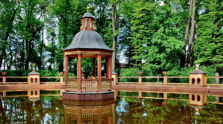 pond with temple-themed wooden gazebo, trees in background