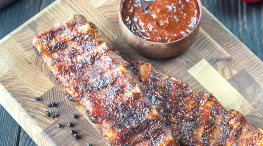ribs with sauce on cutting board
